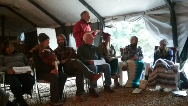 Students in the PDC sitting in a tent in a semi-circle with instructor Rick Longinotti standing and explaining the activity.