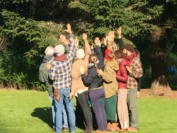 People standing in a tight circle with hands stretched up to the sky