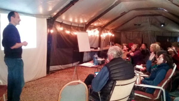 Man standing to the left of a projector screen speaking to a group of people sitting in a tent.