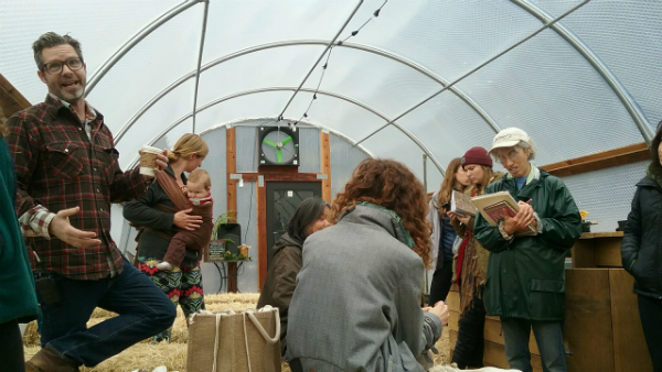 A group of people standing in a hoop house-style greenhouse with one man speaking and other taking notes
