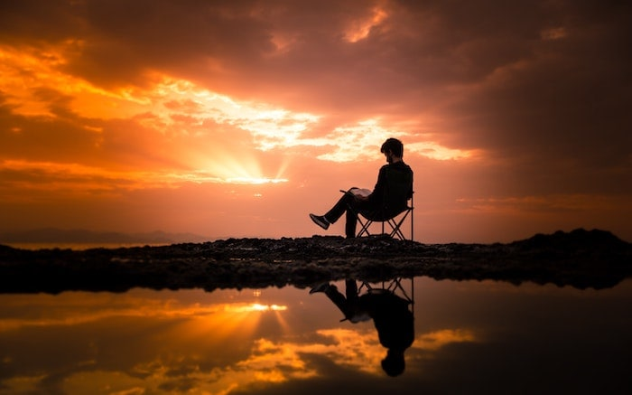 How to Become a Better Reader: Photo of Man Sitting on Camping Chair During Dawn (Photo: Eyüp Belen)