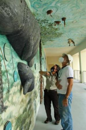 Local artist Lawrence Voytek and Supervisory Refuge Ranger Toni Westland assess damage to the sculptures, how to repair them and how to maintain the valued works of art. Photo provided