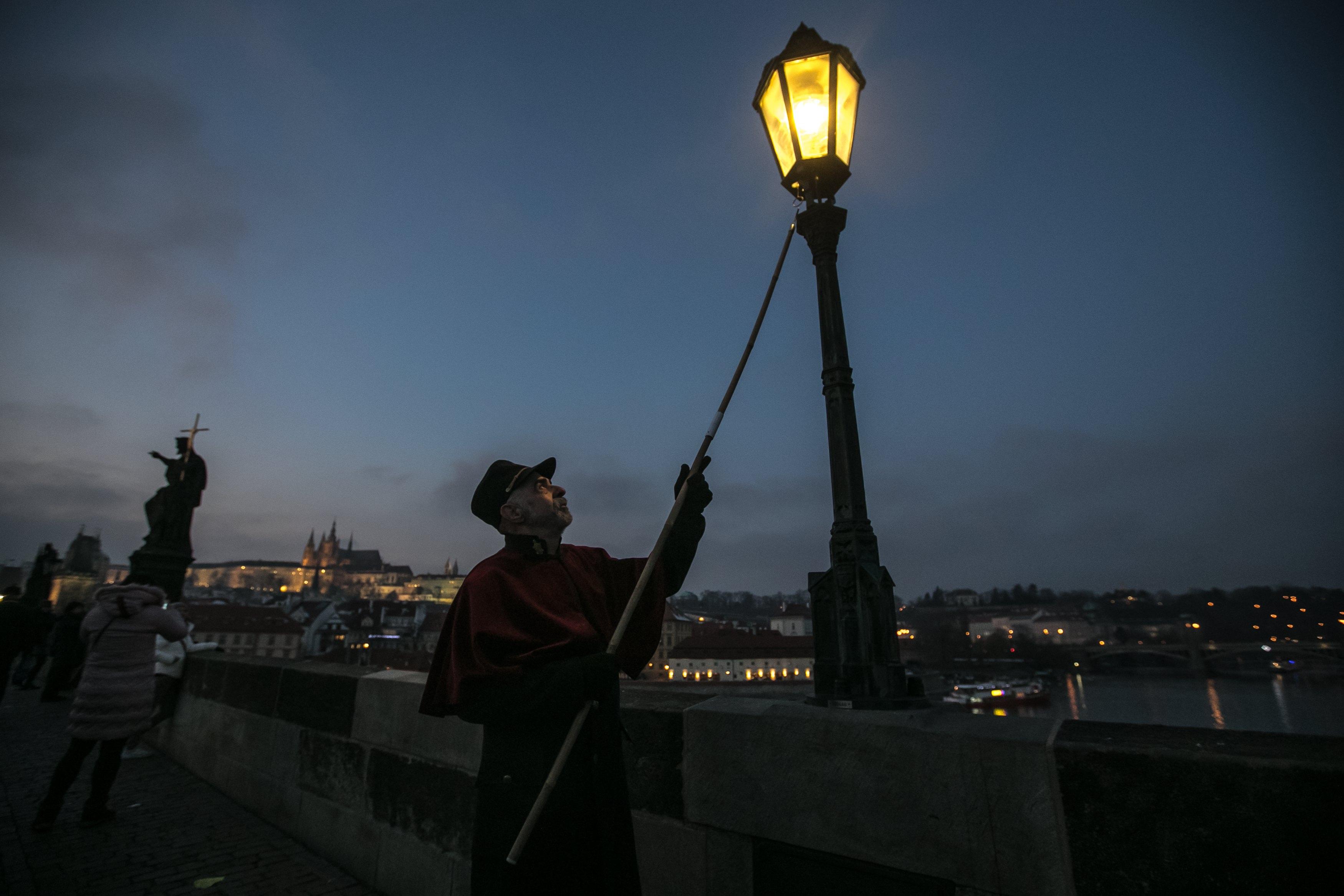 Jan Tater acende um candeeiro a gás na histórica ponte Carlos, em Praga, República Tcheca, dezembro de 2017. Todos os dias, ao anoitecer, durante o Advento, Jan Tater e o seu colega acendem os 37 candeeiros a gás da ponte medieval Carlos, uma atração para turistas. As primeiras lâmpadas de gás na ponte Carlos datam de 1848. EPA / MARTIN DIVISEK
