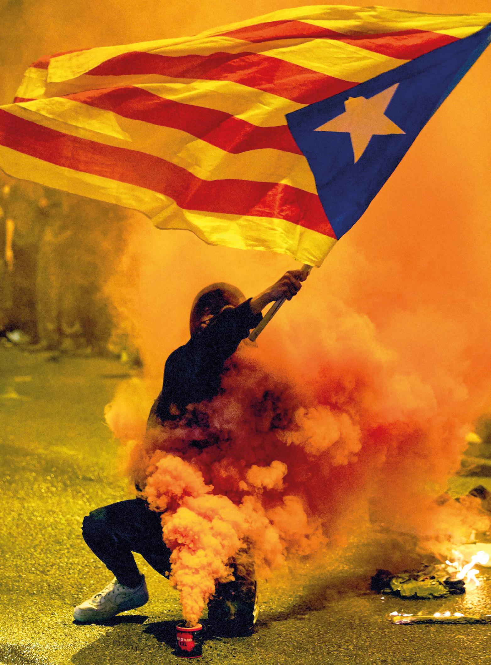 Um manifestante agita a 'Estelada', bandeira não oficial da independência da Catalunha, durante motins contra a decisão da Suprema Corte espanhola de várias penas de prisão para líderes pró-independência. 18 de outubro de 2019. EPA / DAVID BORRAT