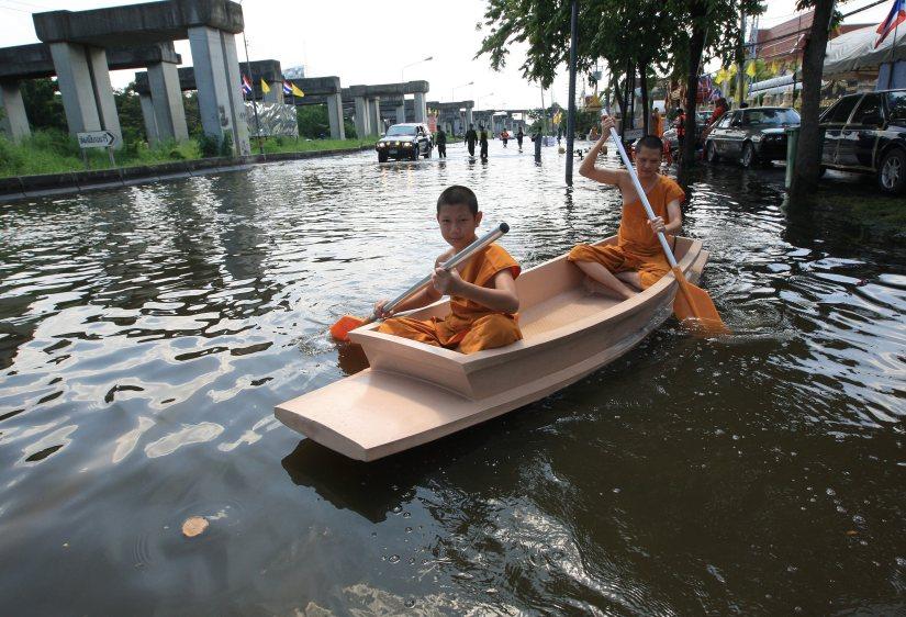 Jovens monges budistas tailandeses usam um barco na estrada local inundada perto do templo Samiennaree em Bangkok, Tailândia, 03 de novembro de 2011. EPA / NARONG SANGNAK