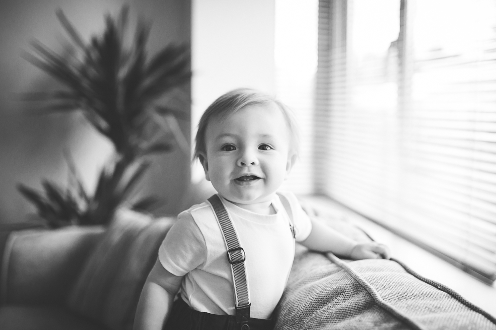 baby boy standing window photo natural light