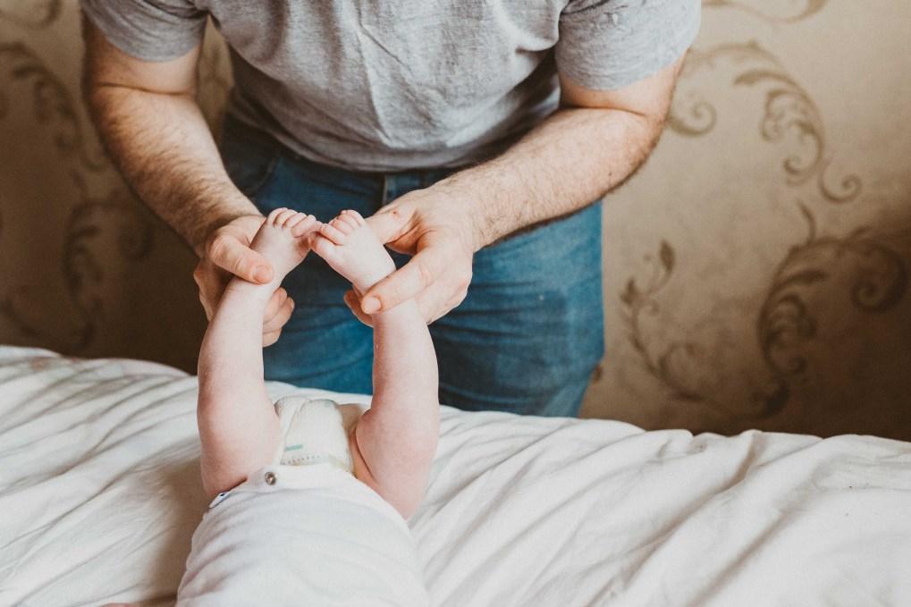 dad holding newborn son feet