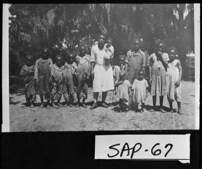 Sapelo_Island_19151934__Young_woman_with_group_of_children_on_Sapelo__Probably_descendants_of_Thomas_Spaldings_slaves