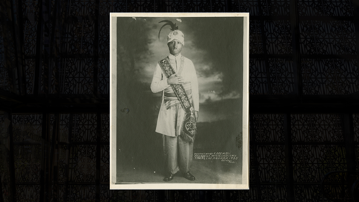 Photograph of Prophet Noble Drew Ali, dressed in ceremonial garments, standing with this right hand over his chest.