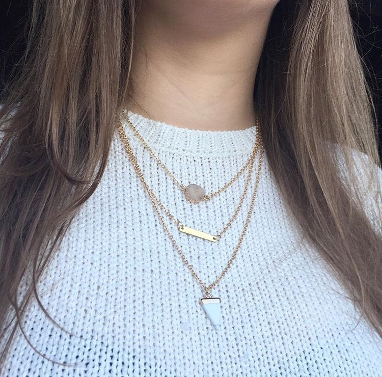 white sweater and gold coloured necklace