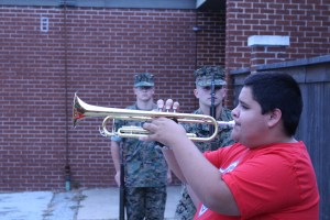 Sapulpa High School Trumpeter Nathaniel Adamson plays Taps alongside the Sapulpa High School Marine Corps JROTC rifle team members (left to right) Cadet 2nd Lieutenant Perry Pry and Cadet Sargent Ford Jacob Ford.