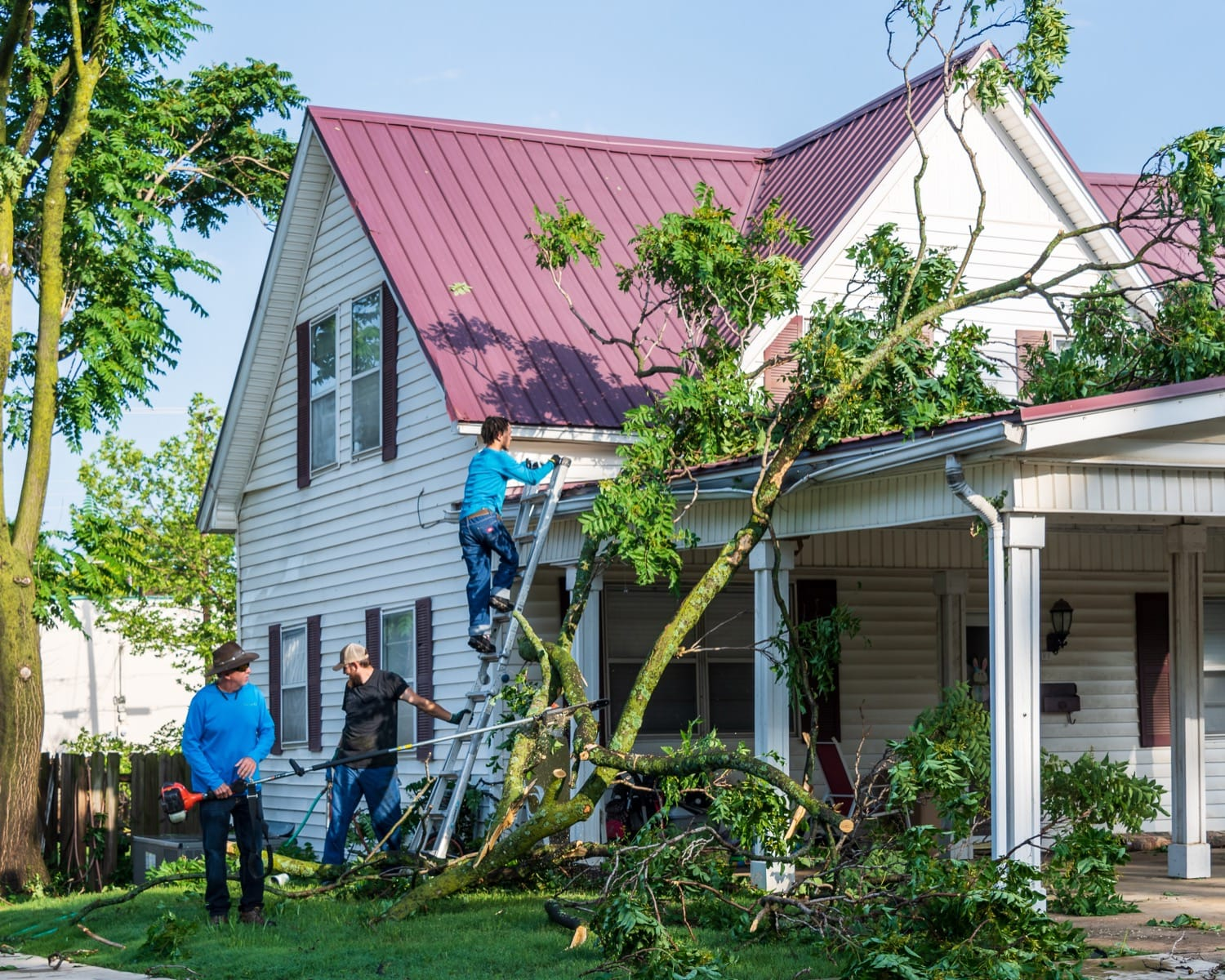 Residents of a Sapulpa home work to remove debris from the roof.