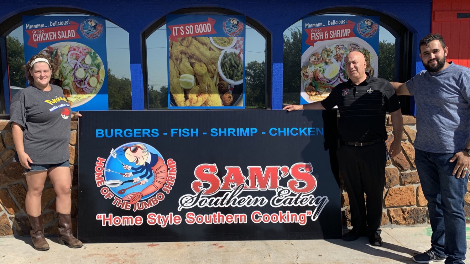 """An unnamed employee, left, stands with site developer M. """"Michael"""" Kalel and """"Mr. Z"""" near the entrance to Sam's Southern Eatery."""