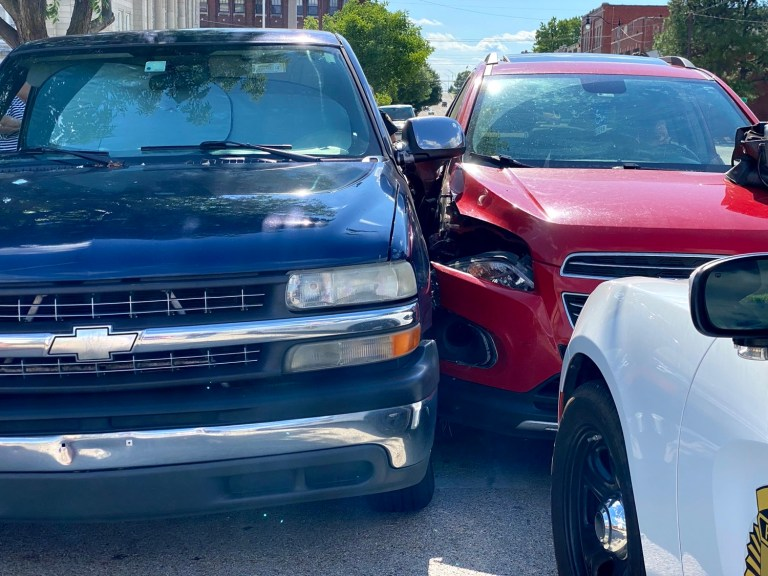 Woman narrowly misses colliding with police, hits parked truck instead