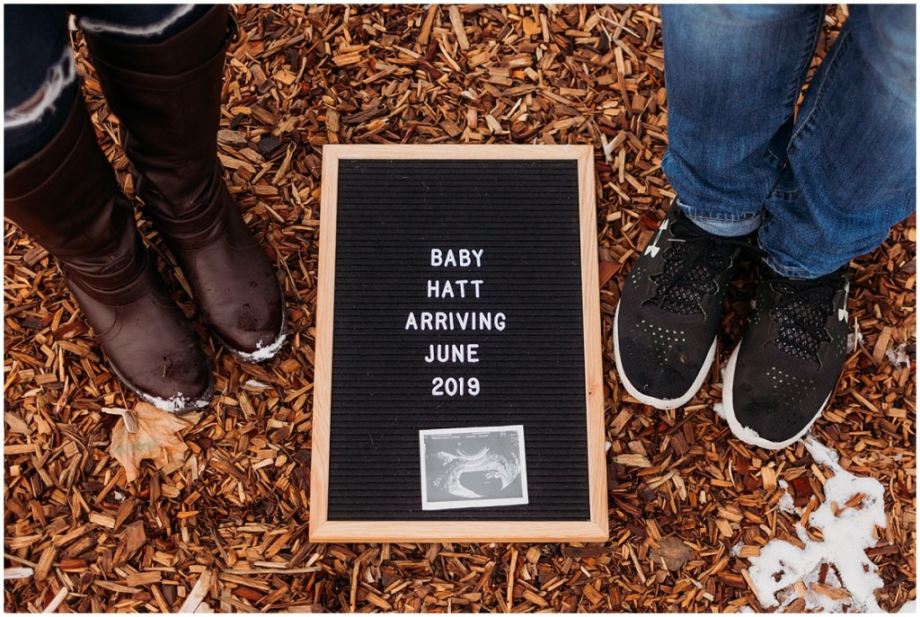 Couple standing with feet by sign for pregnancy announcement in Michigan