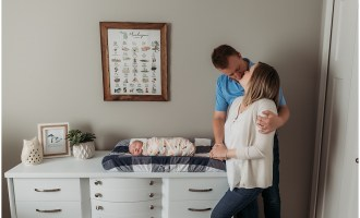Parents kissing next to baby newborn in Brighton MI home