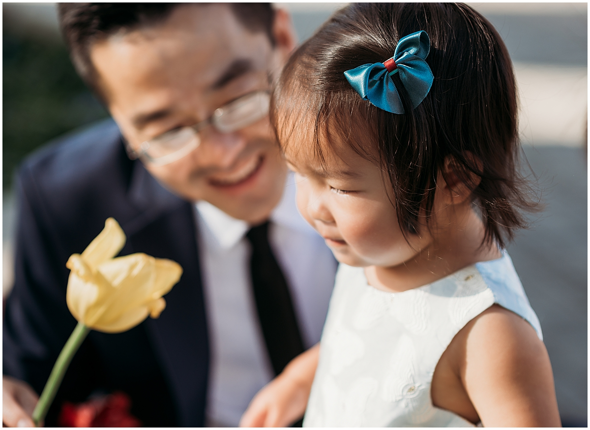 Dad showing daughter a flower