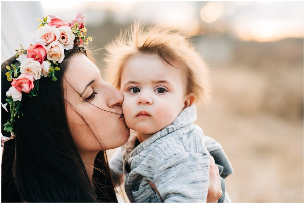 Motherhood Mini Session: Mommy kissing son for a photo in front with the sunset glowing in the background during their photography session in Livingston County Michigan.