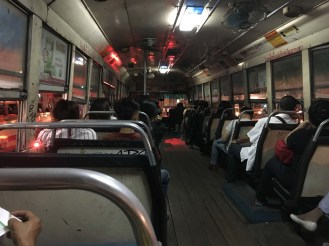 Taking the Bangkok bus. The people sitting next to us helped interpret to pay our fare.