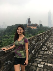 Sarah on the wall with temple and downtown Nanjing visible in background.