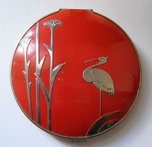 Compact. 1934. Non-spill, red with a heron/stork. Stratton, maker.