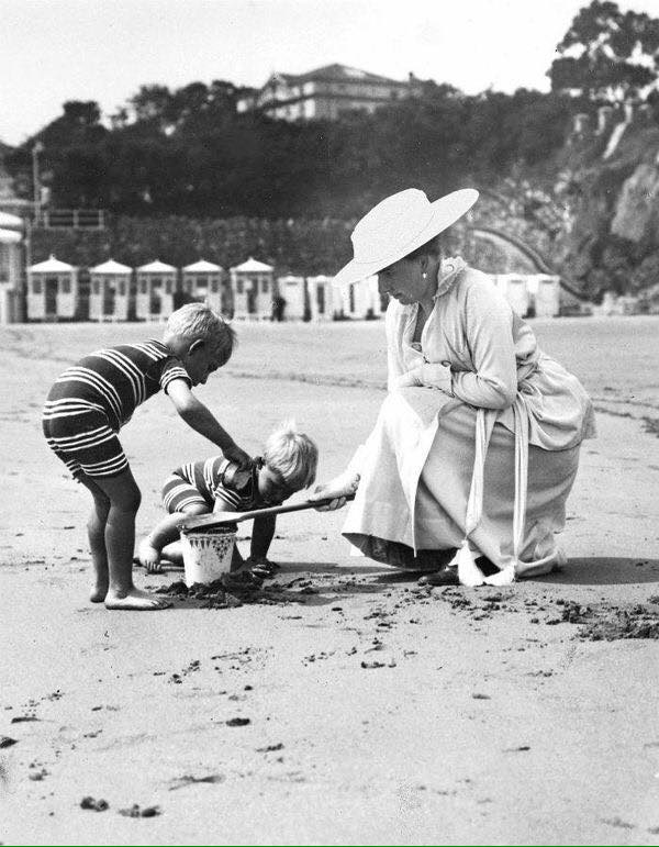 Queen Victoria Eugenia of Spain plays with her two youngest children on the beach. ca. 1916.