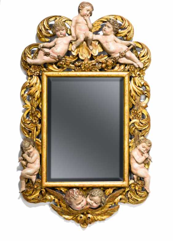 Decorative mirror with putti. Coniferous wood with carved acanthus foliage  acanthus foliage and floral garlands. Three putti at the top. two on the sides and cherubs heads below. Plated. 19th c. in a Baroque style.