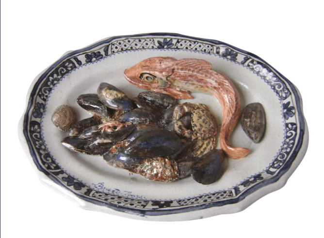 Oval dish decorated with red mullet, a crab, and a seashell in relief.