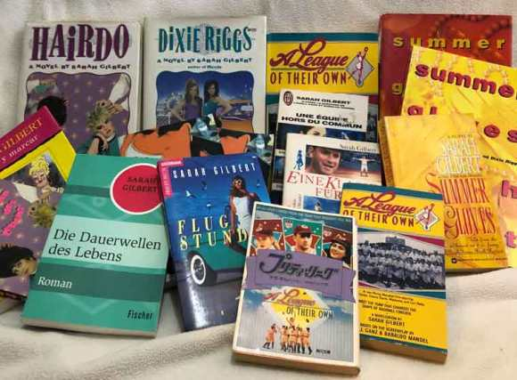 A photo of some of the novels sarah gilbert fox has written, includa photo of some of the novels sarah gilbert fox has written, including: hairdo, a league of their own, summer gloves, dixie riggs, and some of the fourteen languages in which they were published