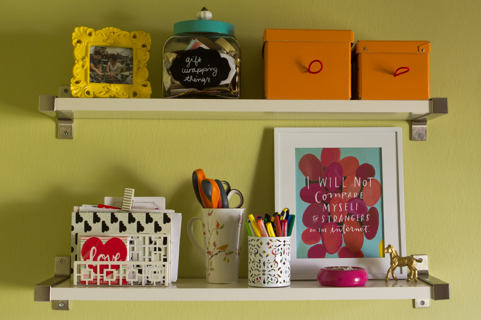 Add a mix of pretty storage containers and art for a functional and stylish storage solution.