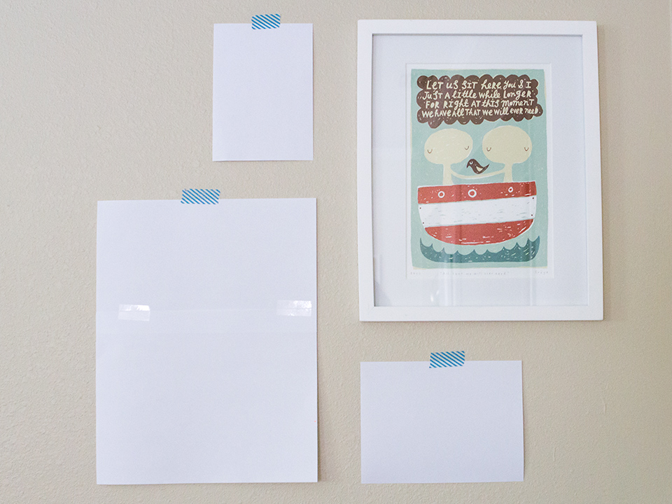 Hanging a gallery wall is easy! Cut printer paper the same size as frames and arrange on the wall using washi tape. Add nails, remove paper, and hang art!