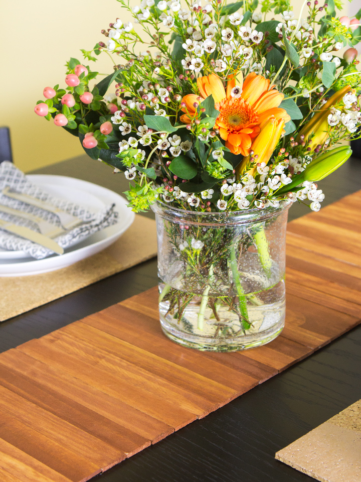 A wood table runner for cheap! Made with stained, paint stir sticks. Click through for video tutorial.