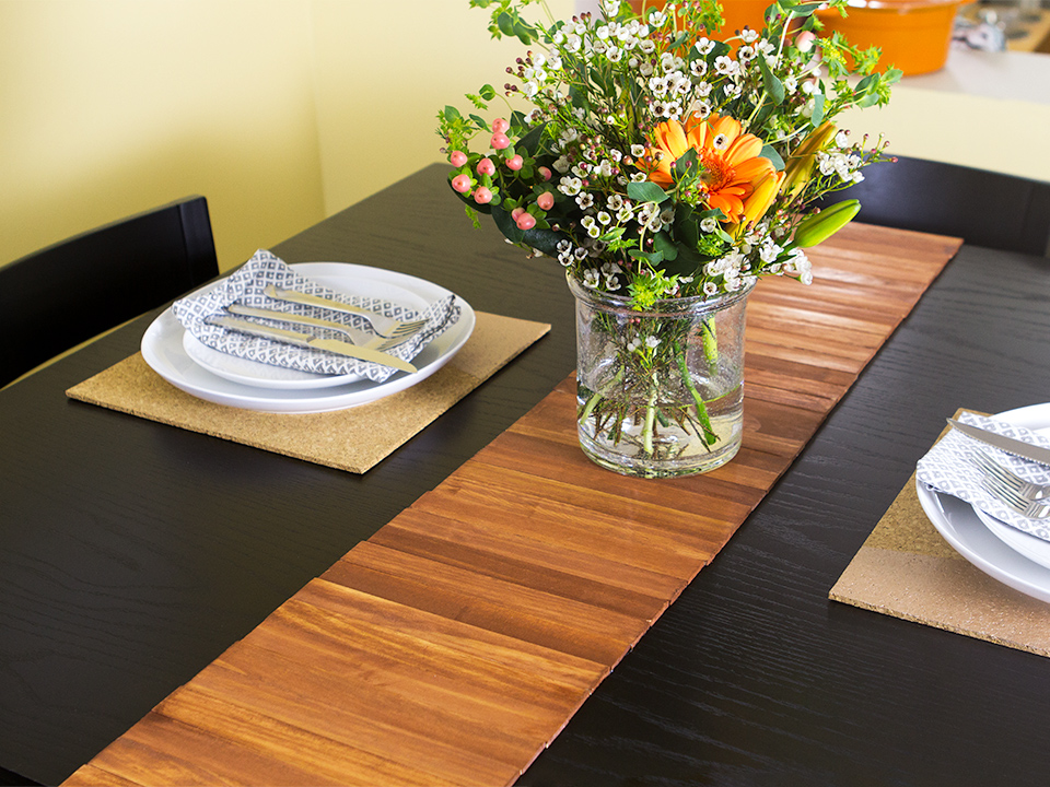 Paint stir sticks are transformed into a stylish wood table runner. (Click through for video tutorial)