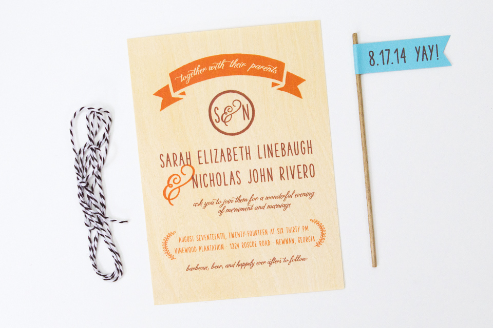These rustic wedding invitations were printed on birch veneer and were wrapped with baker's twine and included these cute little flags.