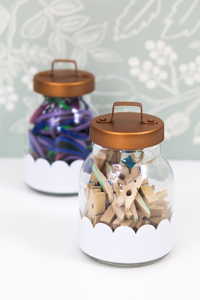 Regular glass canisters with metal lids get a makeover with some white adhesive vinyl and rose gold spray paint.