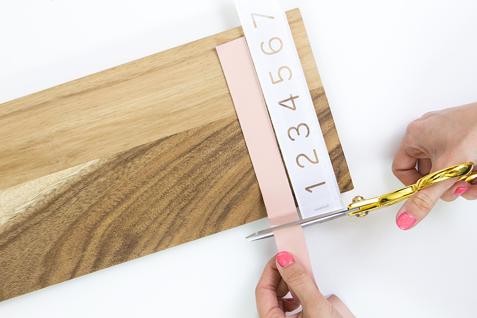 Cut leather strips slightly smaller than the width of a wood board to create handles for a cheese board.