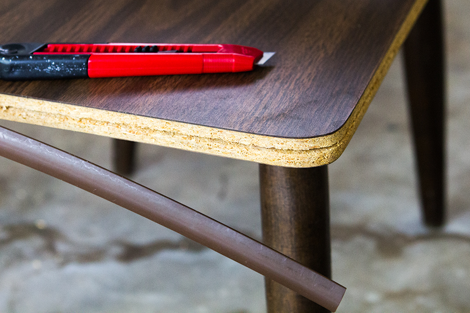 Remove plastic edging on old laminate furniture with a utility knife and replace it with iron on edging tape.
