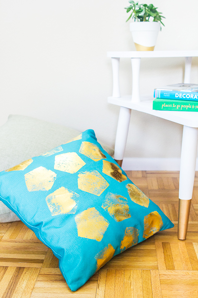 Dress up a solid store bought pillow cover with gold foil! Learn how to make your own statement throw pillow in this step-by-step tutorial.