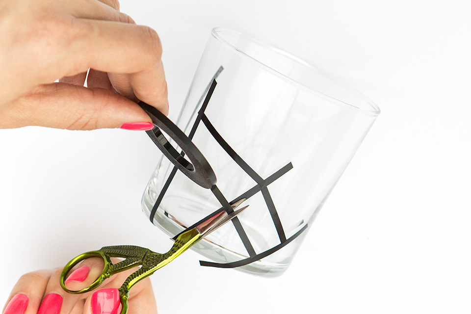 Use black graphic tape to create spider web glassware that's perfect for Halloween!