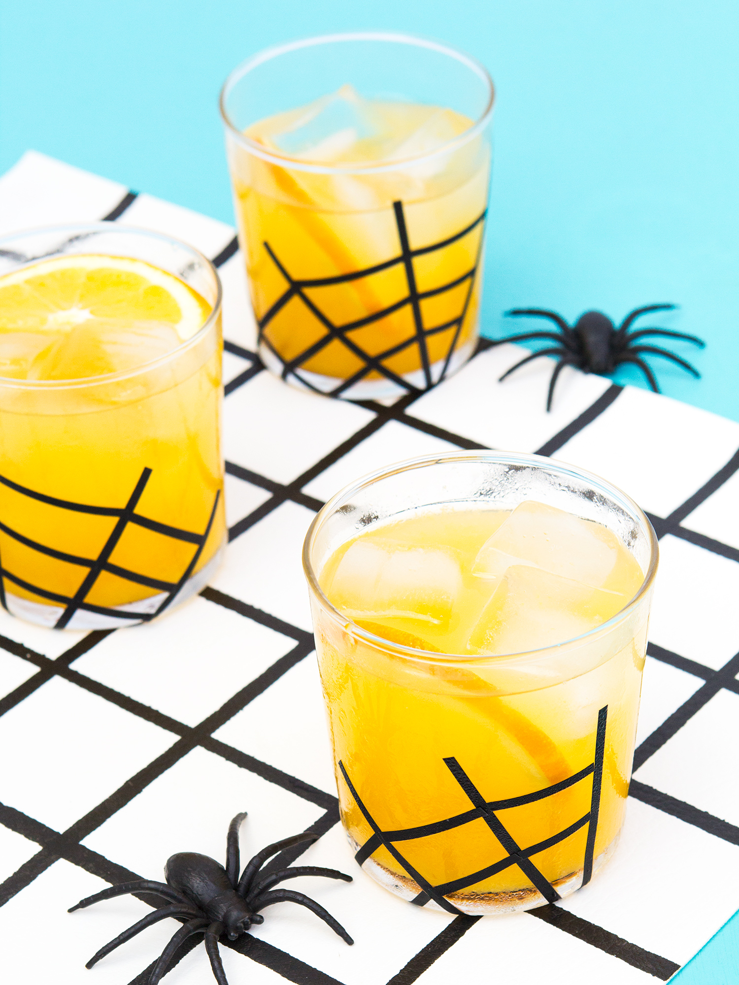 Serve vanilla spiced gin and orange juice at your Halloween party! (Click through for the recipe and to see how to to make your own spider web glassware!)
