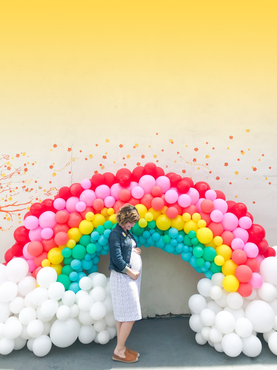Sarah standing under a balloon rainbow arch.