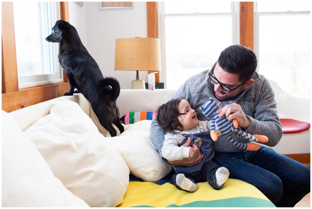 Dad and baby boy snuggling and playing on the couch together while dog looks out the window in Bath Maine