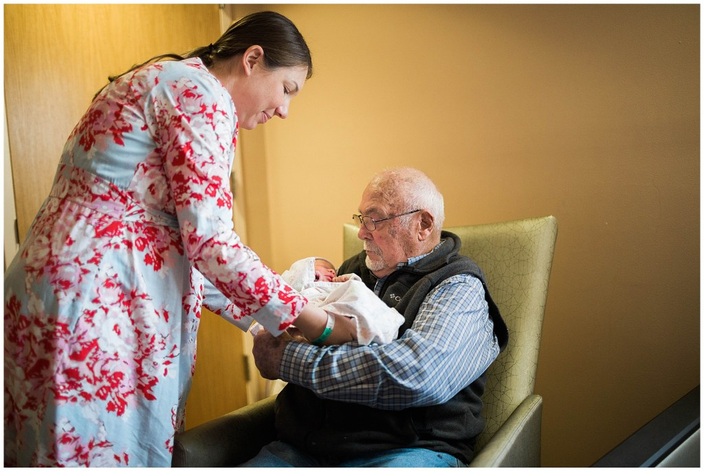 great grandfather holds baby for the first time