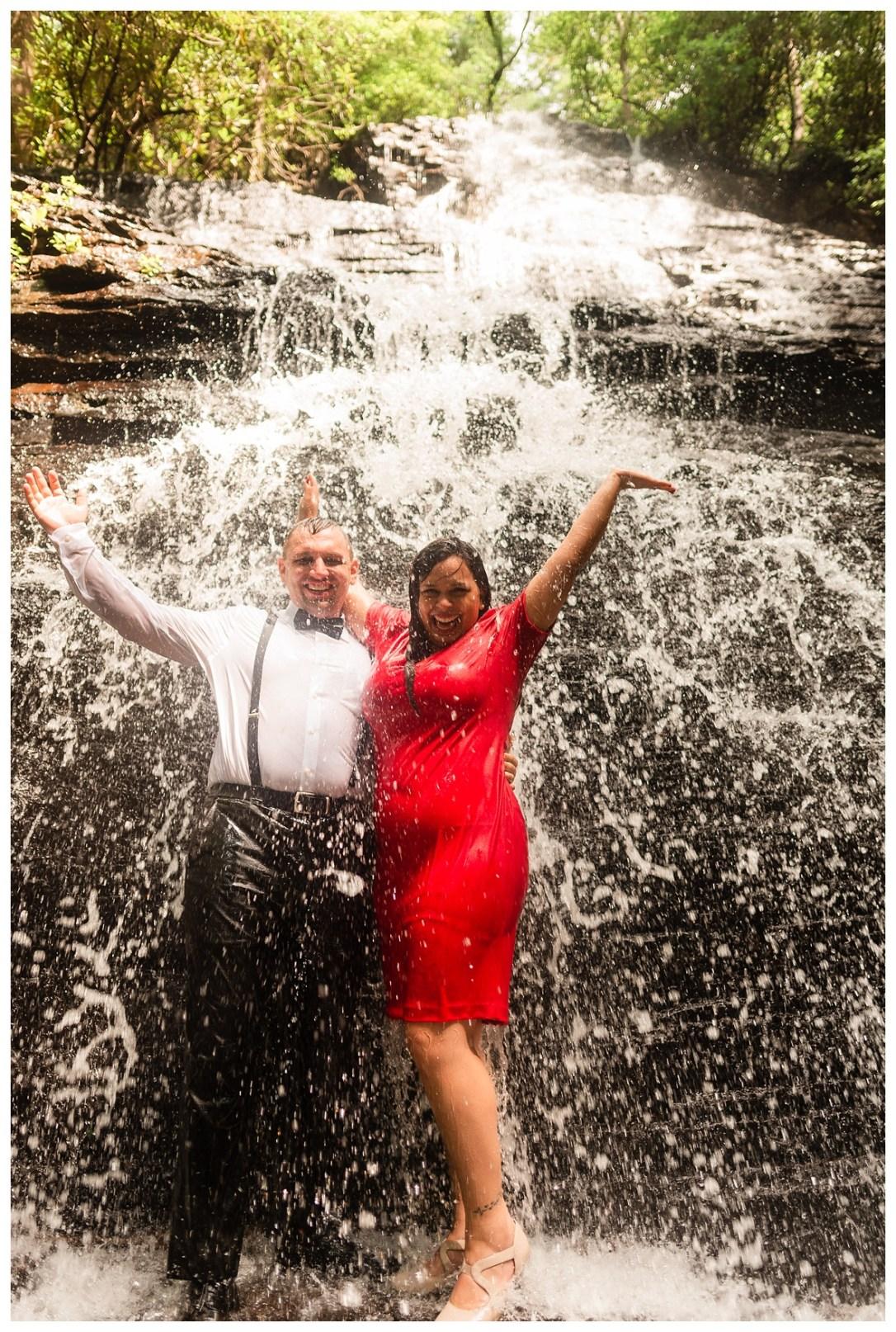 couple cheers under waterfall