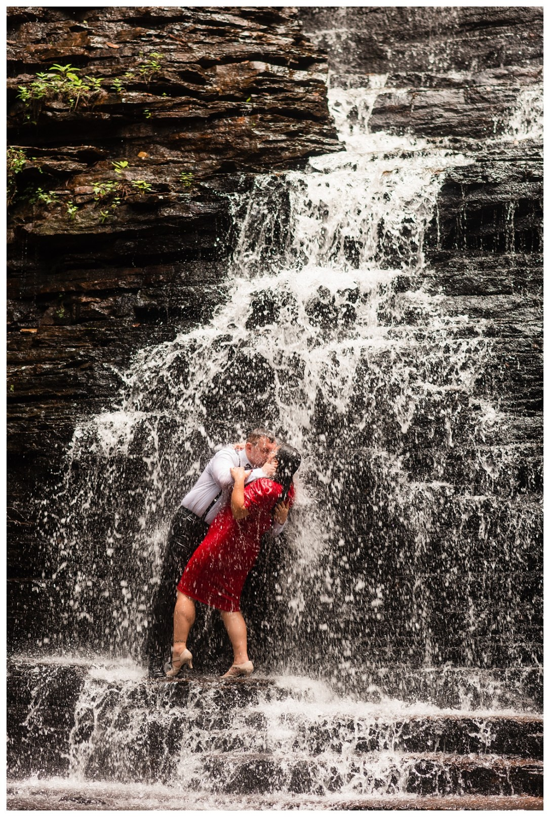 engaged couple kissing under a waterfall