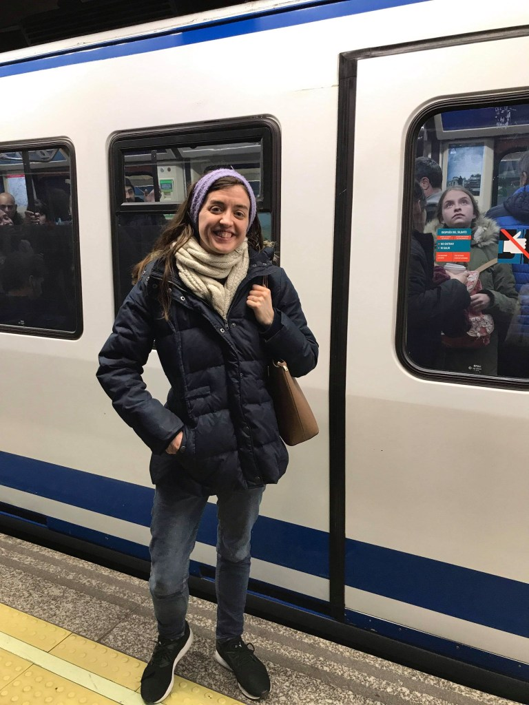 girl in winter coat, purse and scarf standing on metro station platform in front of parked train