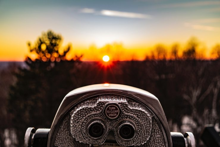 close up of a silver viewfinder looking out across a field at sunset
