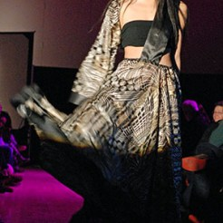 A person with a dress on posing for the camera at a fashion show
