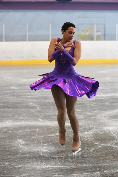 A person in a purple dress spinning during a figure skating competition