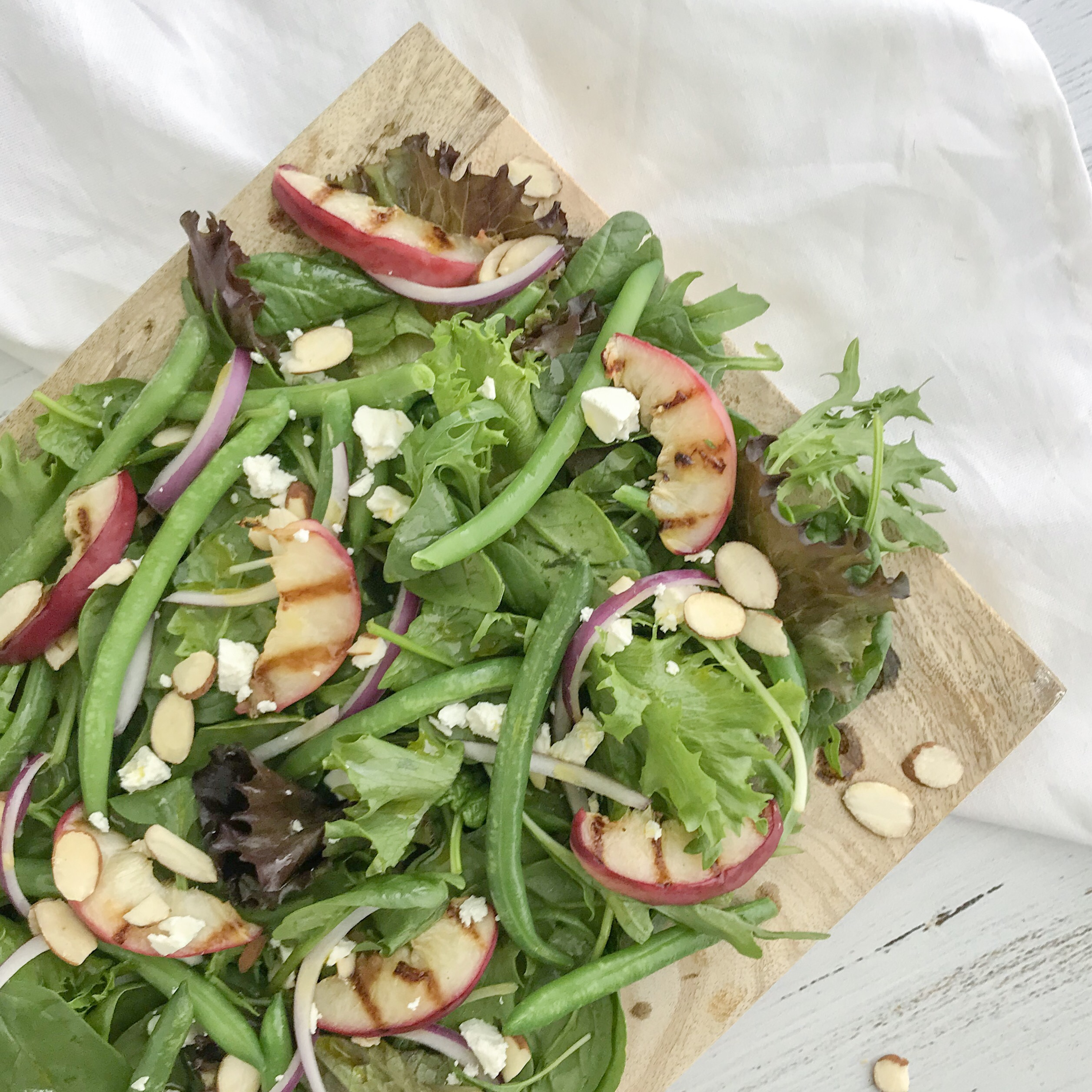 Close up of grilled peach, green bean and almond salad with red onions and crumbled feta